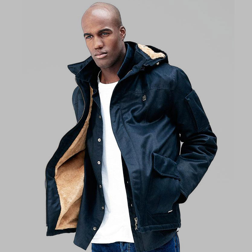 A photograph of a young man wearing a Hoodlamb Tech 4-20 jacket on a grey background. The colour of the jacket is navy, the inside lining is golden/beige.