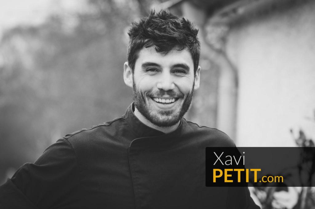 Una fotografía en blanco y negro del Chef Xavi Petit. En el ángulo derecho inferior, en letras grandes, la dirección del sitio web XaviPetit.com está superpuesta a la imagen.