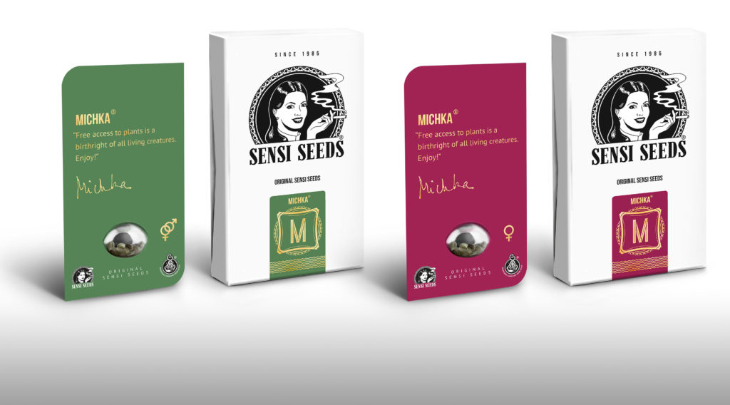 "A photograph featuring the Michka cannabis seeds packaging. From left to right we see a green card with the seeds held in a plastic bubble. Besides the seeds are the interlinked male and female sex symbols. Below the bubble is the Seni Seeds logo and Sensi Seeds medicinal logo. Above the seeds is written ""Michka"" in capital letters, followed by a quote. To the right of the green card is a small white box. On the box is printed a large Sensi Seeds logo, below that is the Michka logo on a green background. The Michka logo features a golden M framed by a indented square and gold decoration. To the right of the white box is a purple card. It share most elements of the green card except it features only the female symbol beside the seed bubble. To the right of the purple card is another white box. It shares most elements with the other white box, except the Michka logo is on a purple background."
