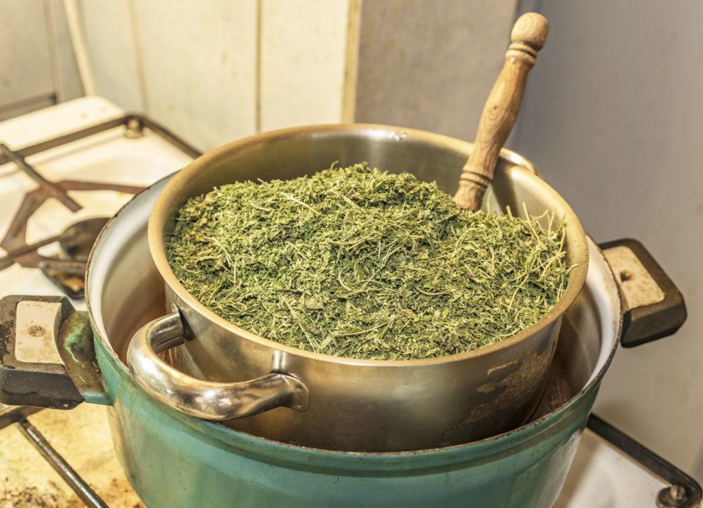Foto eines Kochtopfes auf einem Herd mit einer kleineren Pfanne, die im Kochtopf steht. Die kleinere Pfanne ist gefüllt mit getrockneten Cannabisblüten. Ein hölzerner Löffel stößt durch die Cannabisblüten hindurch.