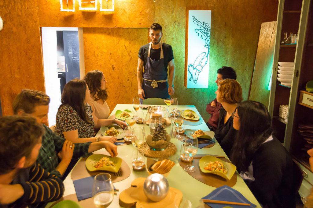 Una fotografía del Chef Xavi Petit de pie en la cabecera de una mesa de comedor. Él está explicando los platos a base de cannabis que están colocados en la mesa en frente de cada invitado. La habitación en la que se encuentran está iluminada brillantemente y las paredes están hechas de madera prensada de tono marrón claro.