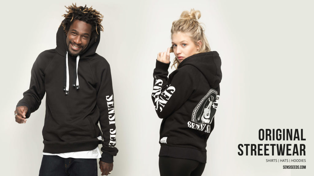 A photograph of a young woman and a man modelling Sensi Seeds original streetwear. He smiles at the camera while she plays with her blonde hair.