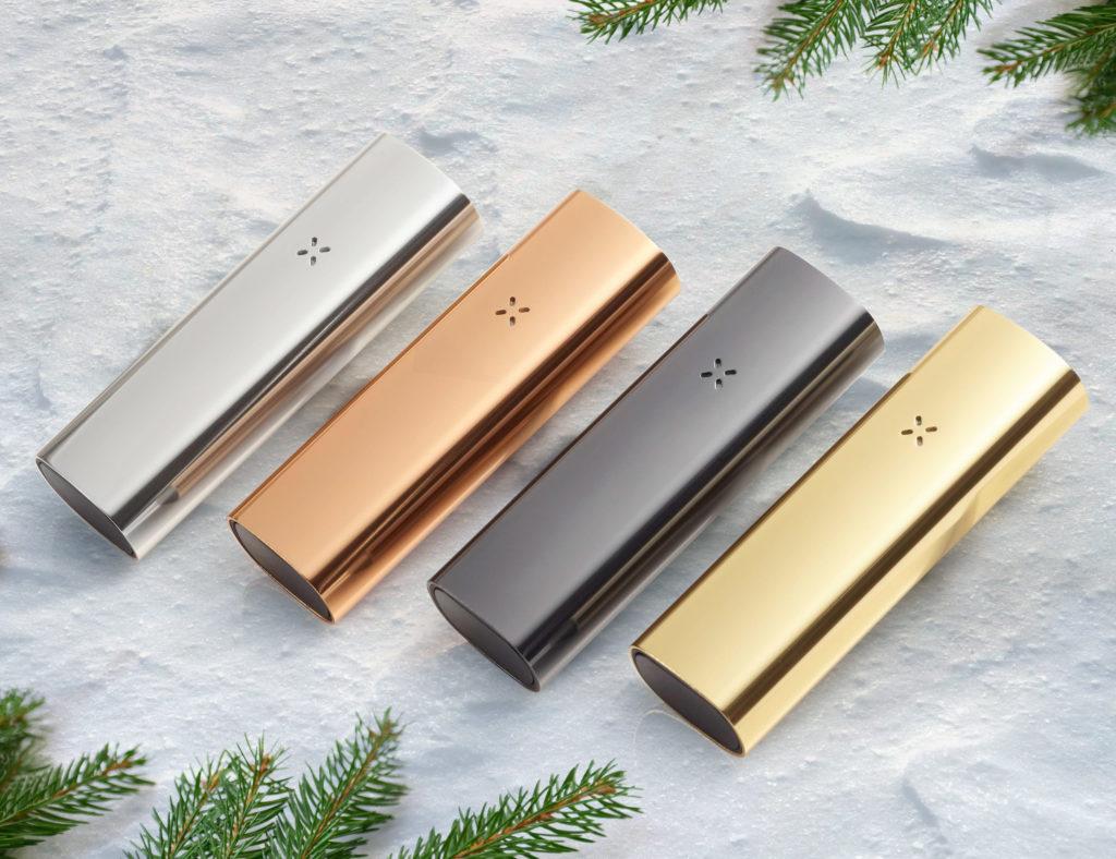 Une photo de 4 vaporisateurs Pax 3, couleurs argent, or rosé, noir et or, sur un fond de marbre gris, les côtés de l'image sont bordés de feuilles de sapin.