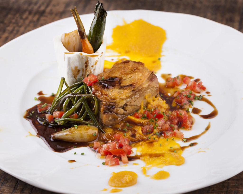 Un plato a base de cordero de vibrantes colores con verduras, salsas y purés de tonos brillantes. El plato se presenta emplatado de forma profesional y elegante.