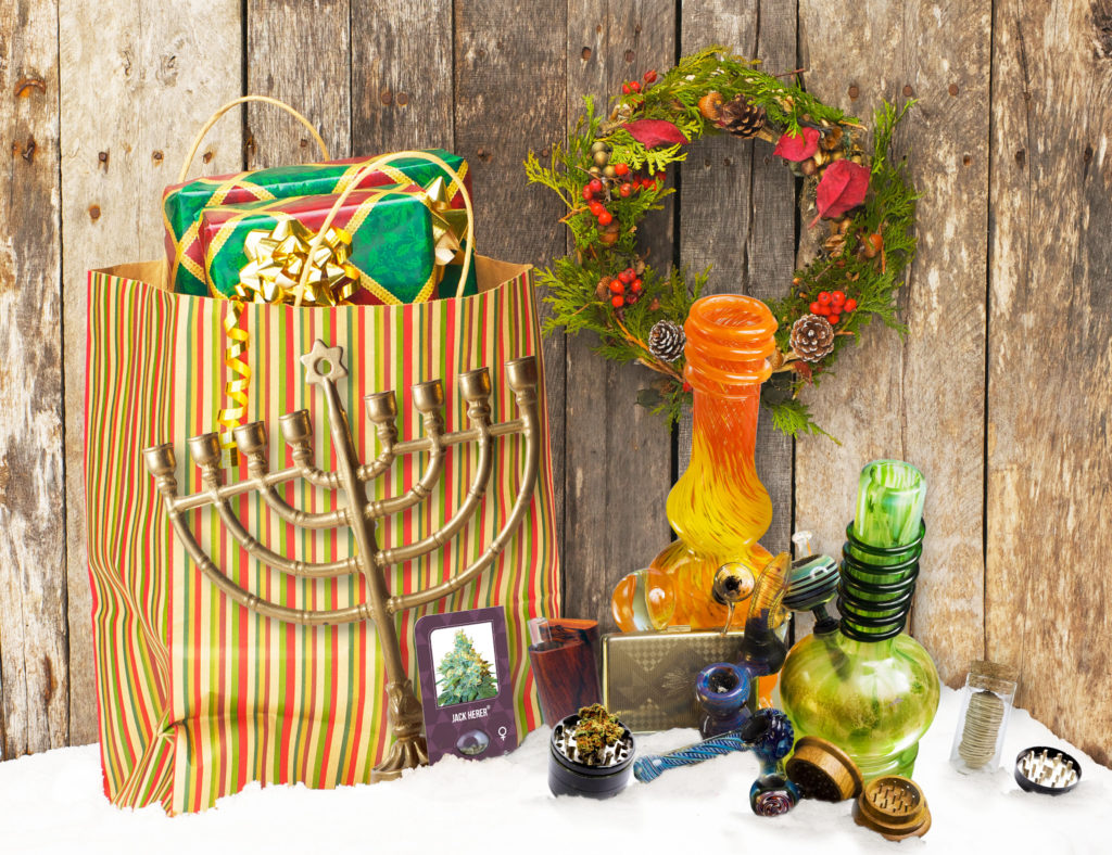 A photomontage showing a variety of items in the snow, next to a big bag with a festive design full of wrapped presents. The items are a pack of Jack Herer Feminized, a dugout, two water pipes, two pipes, two grinders, hemp wicks, and a Chanukkiah.