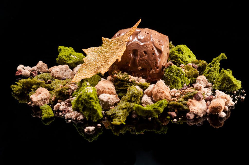 """Una fotografía del plato de postre denominado """"El Bosque Encantado"""" sobre un fondo de color negro. El plato evoca un ambiente botánico. Una gran cucharada de chocolate está rodeada de bizcocho glaseado con terpenos, que le dan un aspecto musgoso. Entre las rebanadas del bizcocho encontramos un crujiente con aspecto de arena."""