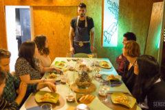 Een foto van Chef Xavi Petit, staande aan het hoofd van een eettafel. Hij vertelt over de cannabisgerechten die op de tafel voor elke gast staan. De ruimte is helder verlicht en de muren bestaan uit lichtbruin geperst hout.