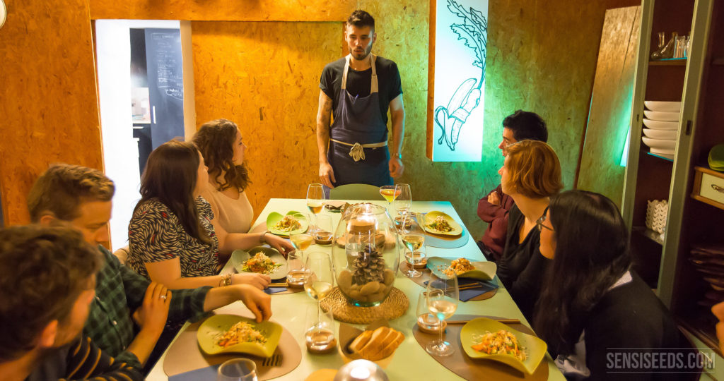 A photograph of Chef Xavi Petit as he stands at the head of a dinner table. He is explaining the cannabis dishes that are placed on the table in front of each guest. The room they are in is lit brightly and the walls are made of light brown pressed wood.