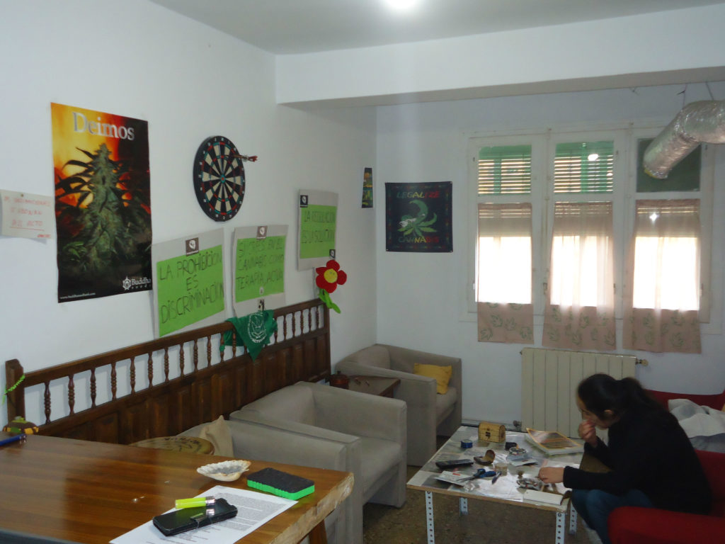 Photo of the premises of a Spanish cannabis club. On the right side of the image, there is a man sitting on a red sofa. In front of him is a side table with smoking paraphernalia. On the walls are posters and a dart board.
