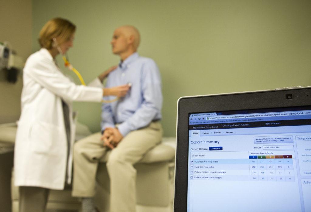 En la parte izquierda de la foto, un poco desenfocada, se ve a una doctora de pie y vestida con bata blanca que ausculta a un paciente sentado en la camilla de la consulta. El paciente lleva una camisa azul y no tiene pelo. En primer plano, la parte inferior derecha, hay una pantalla de ordenador que muestra los datos tomados en una gráfica para la realización de un ensayo clínico.