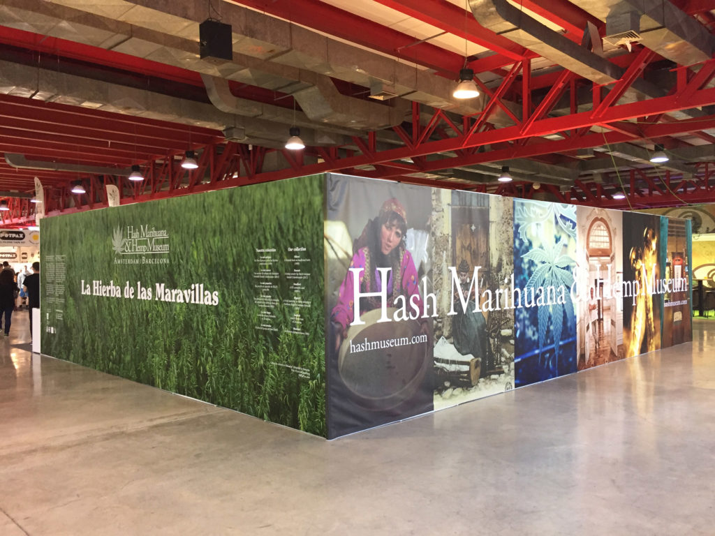 "The exterior of an exhibition stand at Spannabis. The stand is in a convention centre with large red beams fastened to the ceiling. The stand is large and meets at a corner each side featuring a different printed design. The most left part features a large field of cannabis, superimposed is a cannabis leaf logo as well as the words ""Hash Marihuana & Hemp Museum"". Also written is ""La Hieba de las Maravilas"". The most right design features a collection of photos including a woman in traditional dress holding a basket, a figure on a street corner, a cannabis leaf, etc. Here too are the words ""Hash Marihuana & Hemp Museum"" superimposed on the collage, along with website url ""hashmusuem.com""."