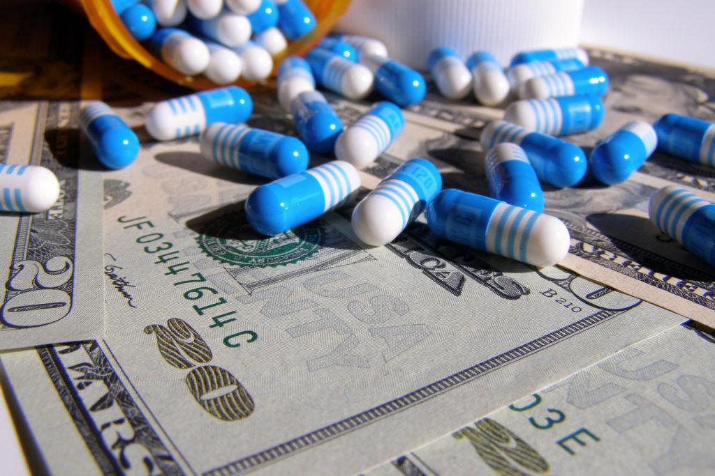 En primer plano en la parte inferior de la imagen, se ve una superficie cubierta por billetes de 20 dólares. Al fondo de la imagen, se ve la mitad de un bote abierto del que salen cápsulas cuyas mitades son: una de color azul y la otra blanca con tres rayas azules, que se esparcen encima de los billetes.