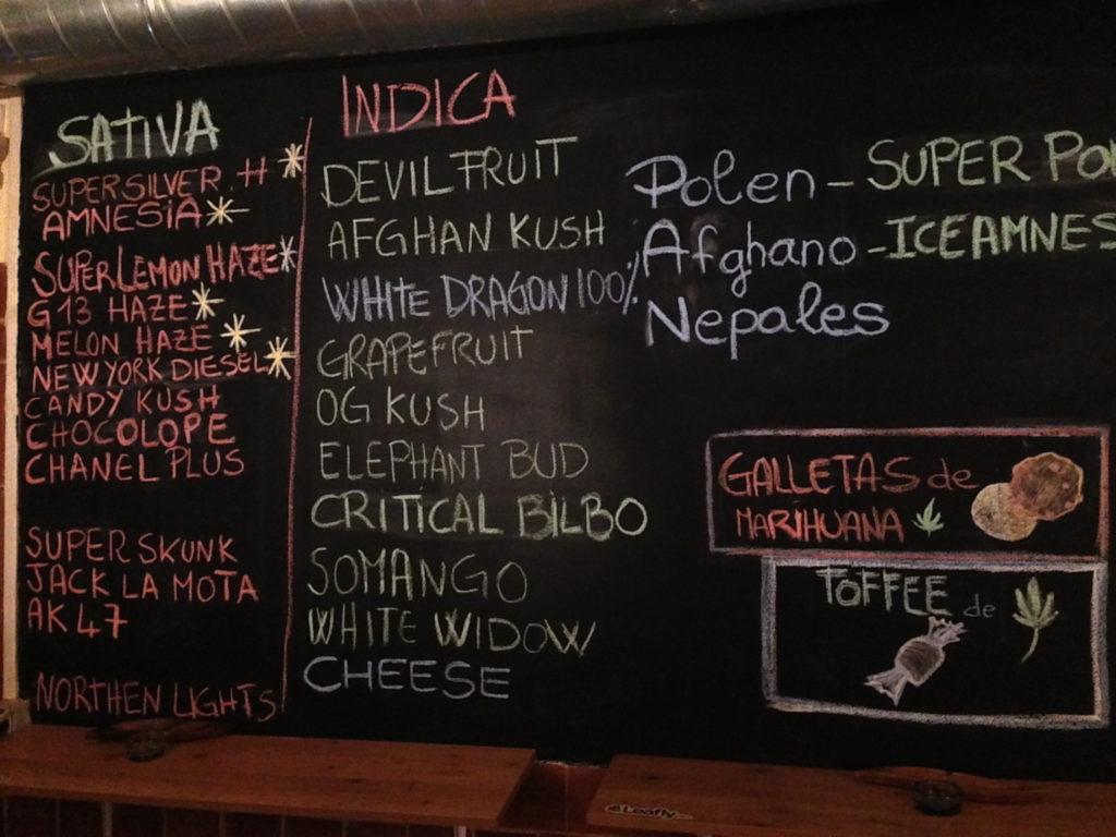 Photo du menu d'un club social espagnol. Le menu est inscrit sur un tableau à l'aide de craies de différentes couleurs, et on peut discerner les sativas des indicas. « Galletas de Marihuana » et « Toffee de Marihuana » sont aussi offerts.