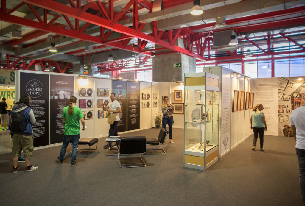 The interior of the Hash Marihuana & Hemp Museum stand at Spannabis. People are standing, looking, and reading the exhibition information which includes posters, artworks, and artefacts related to cannabis history. Low sitting black chairs are placed near the centre. The exhibition space is large and big red beams run along the ceiling.
