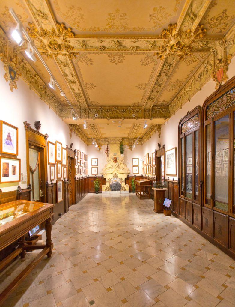 Foto de una hermosa sala del Palau Mornau, sede del museo en Barcelona. Hay cuadros en las paredes y varias vitrinas de madera. En la pared del fondo, hay una chimenea artesonada. Sobre la chimenea, hay un busto con un porro de cannabis en la boca en el centro; a su izquierda, una argila, y a la derecha, una planta de marihuana viva.