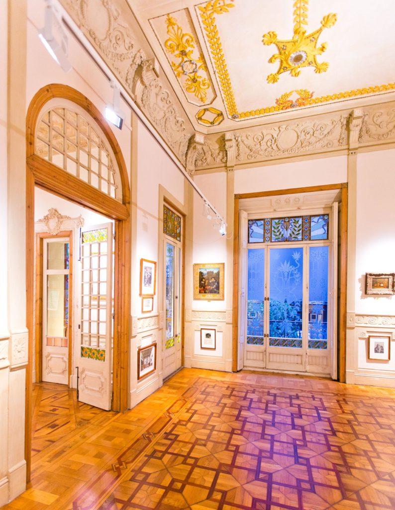 Het interieur van de Hemp Museum-galerie in Barcelona. De foto is kleurrijk en laat voornamelijk de kleuren bruin, goud en blauw zien met groene accenten. Aan de muren van de ruimte hangen schilderijen en tekeningen. De houten vloer heeft een geometrisch patroon. De grote deuren links van de afbeelding zijn geopend en leiden naar de volgende ruimte. De geopende deuren zijn wit en hebben een glazen middenstuk. De onderste en bovenste rij glas is beschilderd met kleurrijke bloemen.