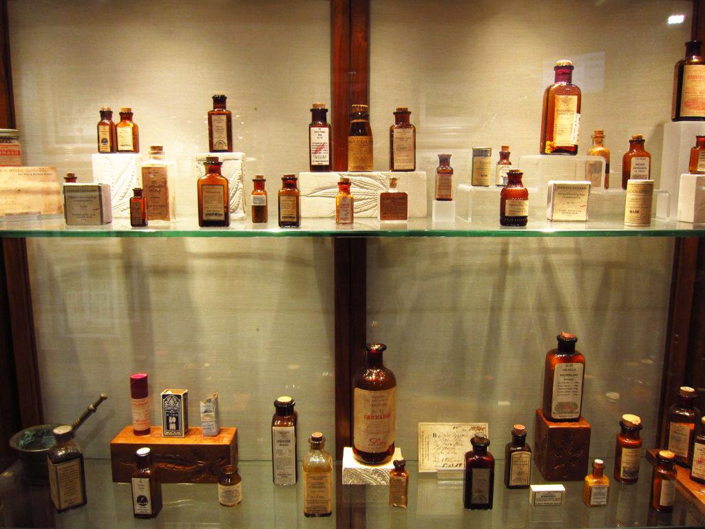 Foto de varios objetos de la colección expuestos. En el centro, sobre una vitrina de cristal, un frasco antiguo de cannabis medicinal. A la izquierda, el cartel explicativo del cuadro que se ve parcialmente al fondo. A la derecha, otra botella antigua de cannabis medicinal.