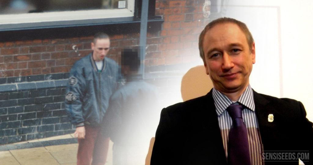 Fotografía actual de Neil Woods de pie delante de una proyección de una imagen de sus días como ex agente infiltrado de la brigada de drogas. Lleva puesto un traje negro y corbata morada.