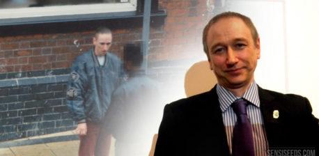 Een foto van Neil Woods nu, die voor een projectie staat van een afbeelding uit zijn tijd als infiltrant voor een narcoticabrigade. Hij draagt een zwart pak met paarse stropdas.