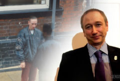 A contemporary photograph of Neil Woods standing in front a projection of an image of his days as a of former undercover drugs squad officer. He wears a black suit and purple tie.