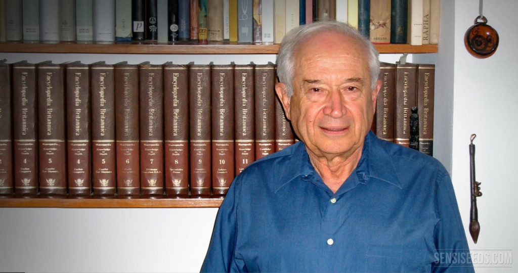 A portrait photograph of Raphael Mechoulam, an Israeli organic chemist and professor of Medicinal Chemistry at the Hebrew University of Jerusalem in Israel. He stands in front of  a bookshelf filled with encyclopaedias. He wears a blue button up shirt and has white hair. He looks into the camera with a slight smile.