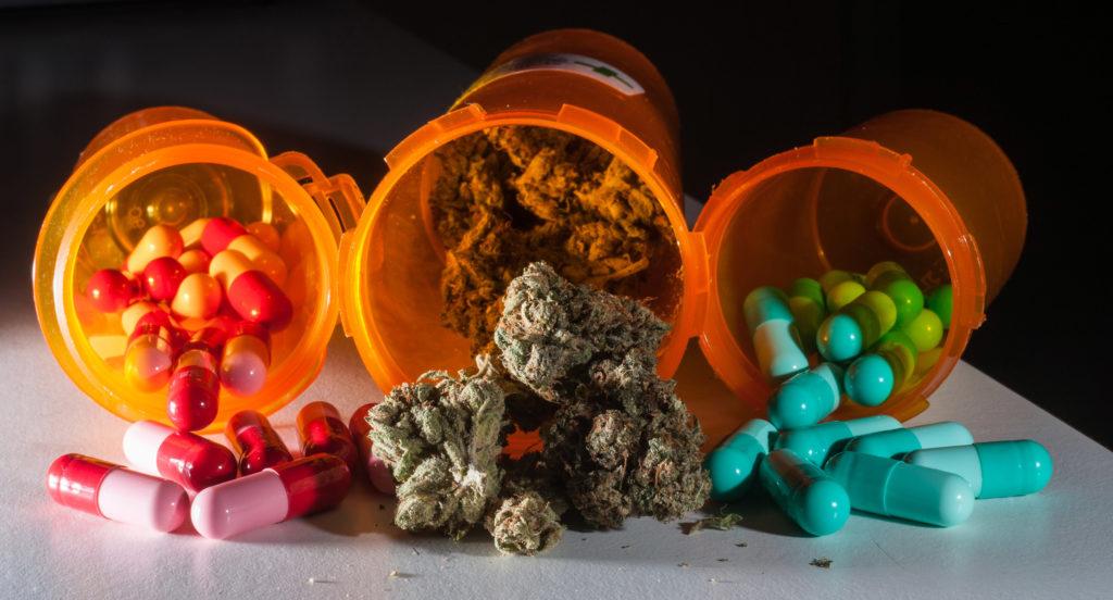 Fotografía de cannabis y pastillas farmacéuticas que se derraman de unas botellas naranjas sobre una superficie.