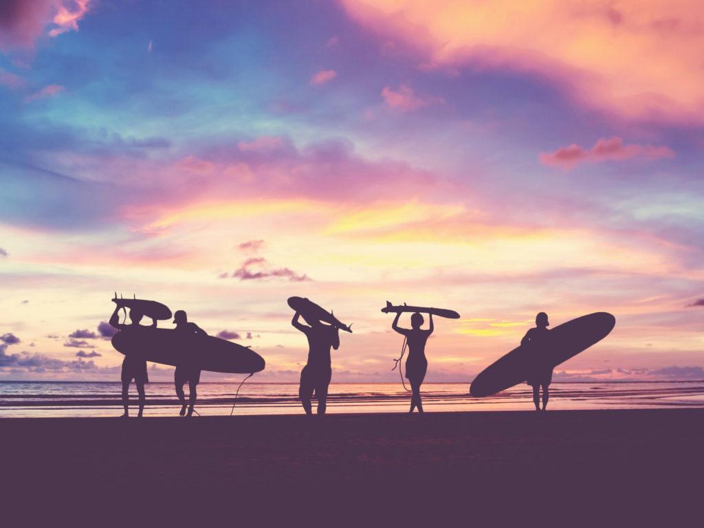 Ein Foto in einem weichen Stil mit Vintage-Filtereffekt, das eine magentafarbene Silhouette von Surfern zeigt, die ihre Surfbretter bei Sonnenuntergang an einen Strand tragen.