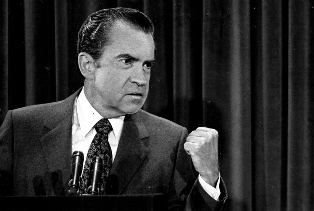 A black and white photograph of President Richard Nixon at a podium holding a fist.