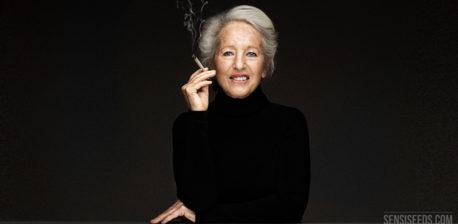 Retrato fotográfico de Michka Seeliger-Chatelain, activista del cannabis. Está sentada detrás de una mesa de escritorio gris delante de una pared gris oscura. Sujeta un porro en la mano cerca de la boca. Va vestida todo de negro. Sonríe ligeramente a la cámara.