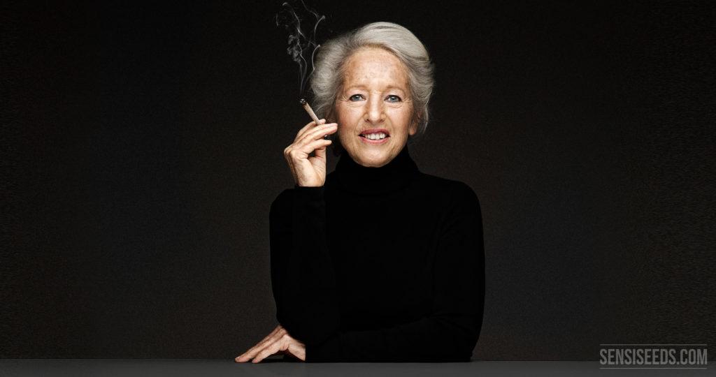 Een portretfoto van Michka Seeliger-Chatelain, cannabisactivist. Ze zit achter een grijs bureau dat voor een donkergrijze muur staat. In haar hand houdt ze een joint bij haar mond. Ze draagt zwarte kleding en glimlacht lichtjes naar de camera.