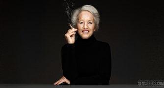 Ein Porträtfoto von der Cannabis-Aktivistin Michka Seeliger-Chatelain. Sie sitzt hinter einem grauen Schreibtisch vor einer dunkelgrauen Wand. Sie hält einen Joint in der Hand, nahe ihres Mundes.