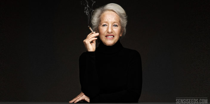 A portrait photograph of Michka Seeliger-Chatelain, cannabis activist. She sits behind a grey desk in front of a dark grey wall. She holds a joint in her hand near her mouth. She wears all black. She smiles lightly to the camera.