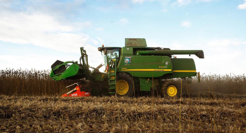 Photo d'un tracteur dans un champ en train de récolter du chanvre. Le tracteur est vert et ses roues sont jaunes. Le champ est brun.