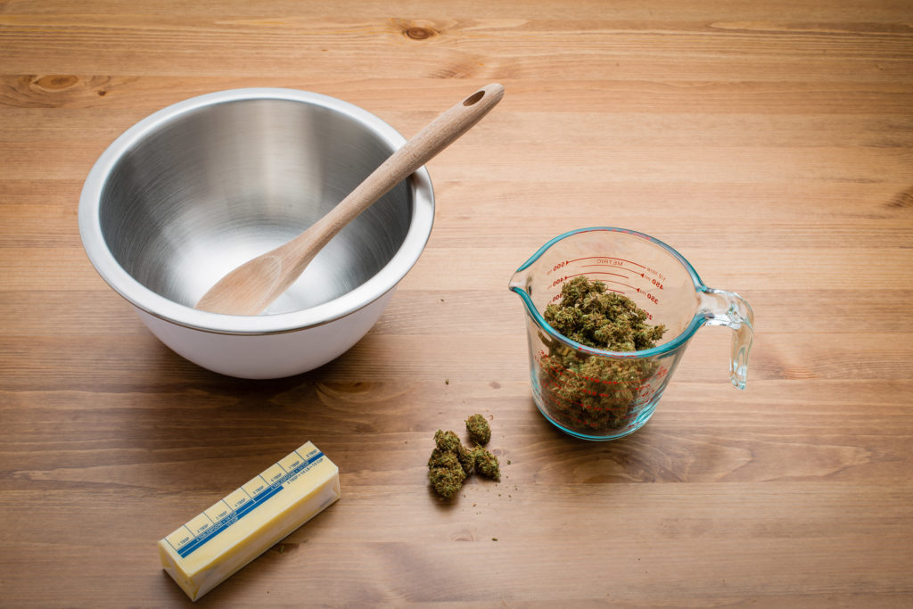 A photograph depicting cooking with a cannabis. On a wooden table we see a metal mixing bowl with a wooden spoon, a glass measuring  cup filled with cannabis nuggets, and a stick of butter.