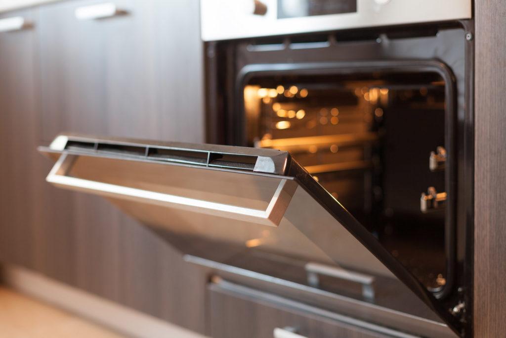 Een foto van een lege, open elektrische heteluchtoven. Het is een nieuwe oven. De klep staat open en het lichtje is aan.