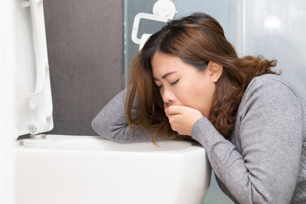 A photograph. A woman leans over a toilet bowl, with one hand behind her head, and another covering her mouth. Her eyes are shut. She either just has, or just will, vomit.