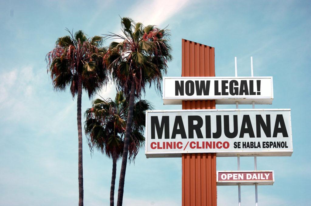 """Een foto van palmbomen, een blauwe lucht en reclameborden waarop staat: NOW LEGAL MARIJUANA. CLINIC/CLINICO. SE HABLA ESPANOL. OPEN DAILY."""" Het lijkt op de omgeving van Californië."""