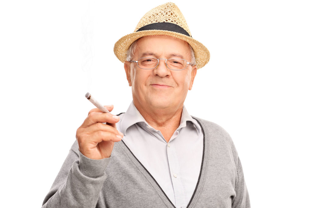 A photograph showing an elderly man, wearing a grey cardigan, over a grey button up t-shirt, and a straw hat. He holds a large joint in his fingers. He looks into the camera and has a slight smile.