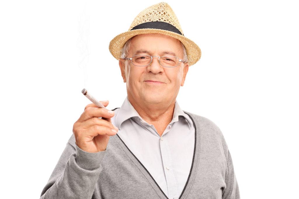 Een foto van een oudere man, hij draagt een grijs vest over een grijs overhemd, en een strohoed. Hij houdt een grote joint tussen zijn vingers. Hij kijkt in de camera en glimlacht een beetje.