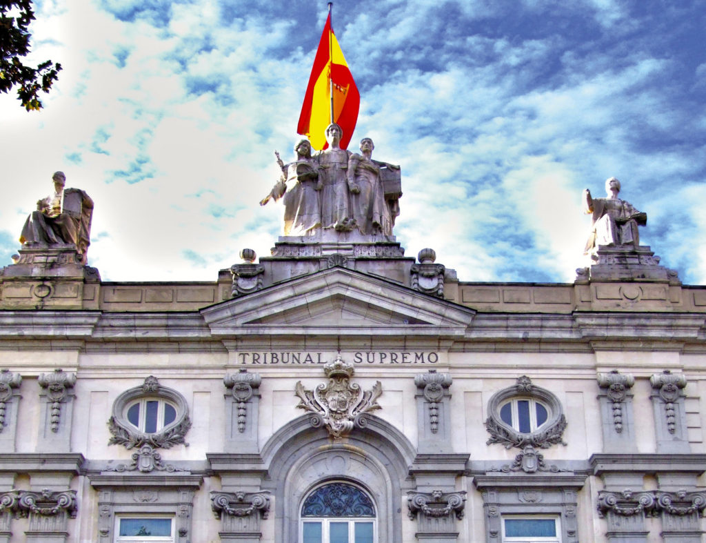 A photograph showing the Supreme Court of Spain, or the Tribunal Supremo de España. It is an ornate building, imposing, with multipe sculptures of human figures, and a large Spanish flag on top. The sky behind the building is cloudy and bright blue.