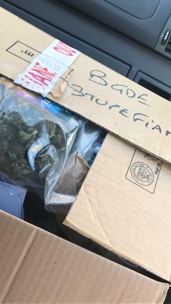 Foto eines Kartons auf dem Beifahrersitz eines Autos. Der Karton ist halb geöffnet und es sind Plastiktüten mit getrockneten Cannabisblüten sichtbar. Auf dem Karton steht mit schwarzem Marker: BGDE STUPEFIANT