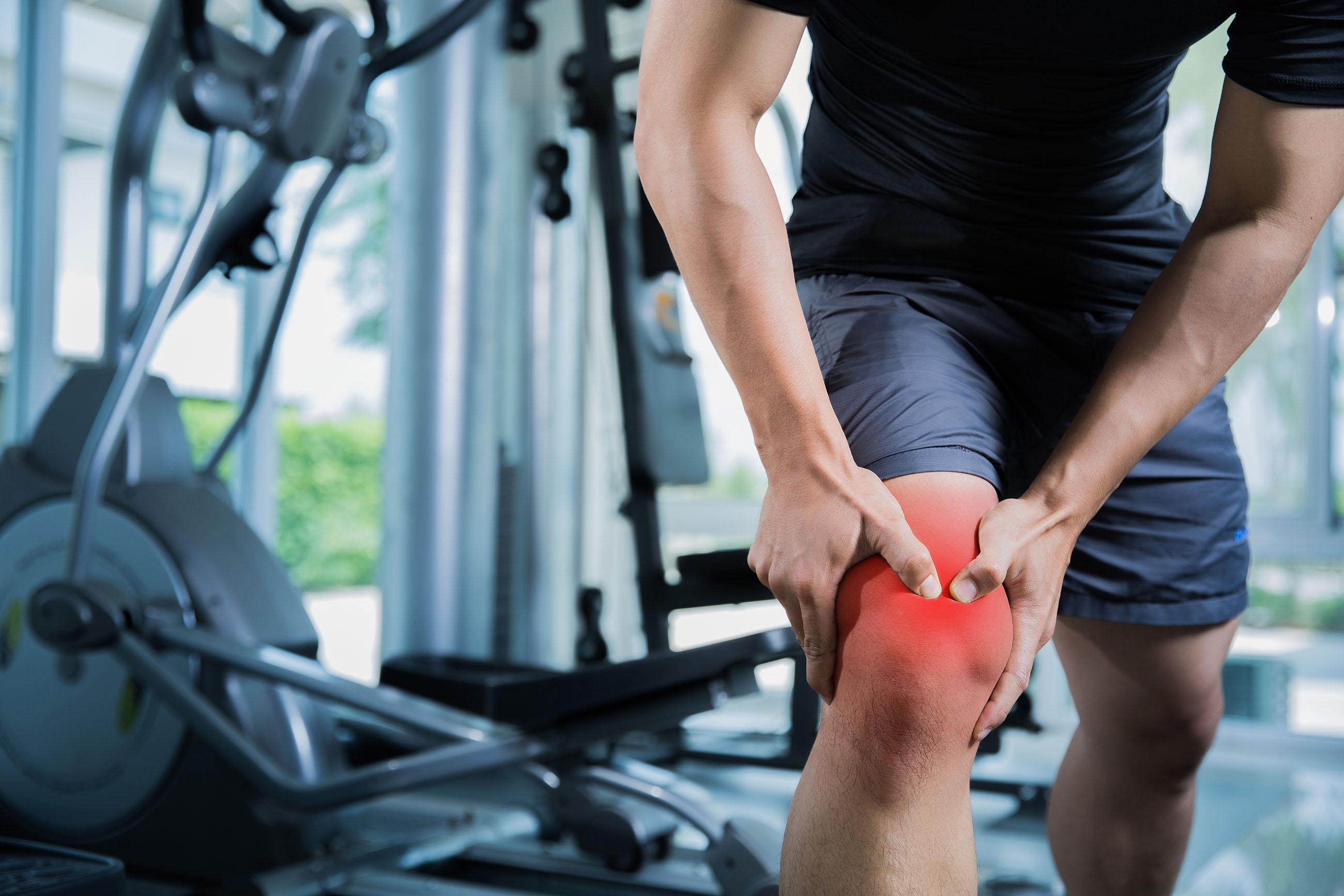 La fotografía muestra la parte inferior del cuerpo de un hombre en un gimnasio. La rodilla del hombre está roja y se la está sujetando con las dos manos.