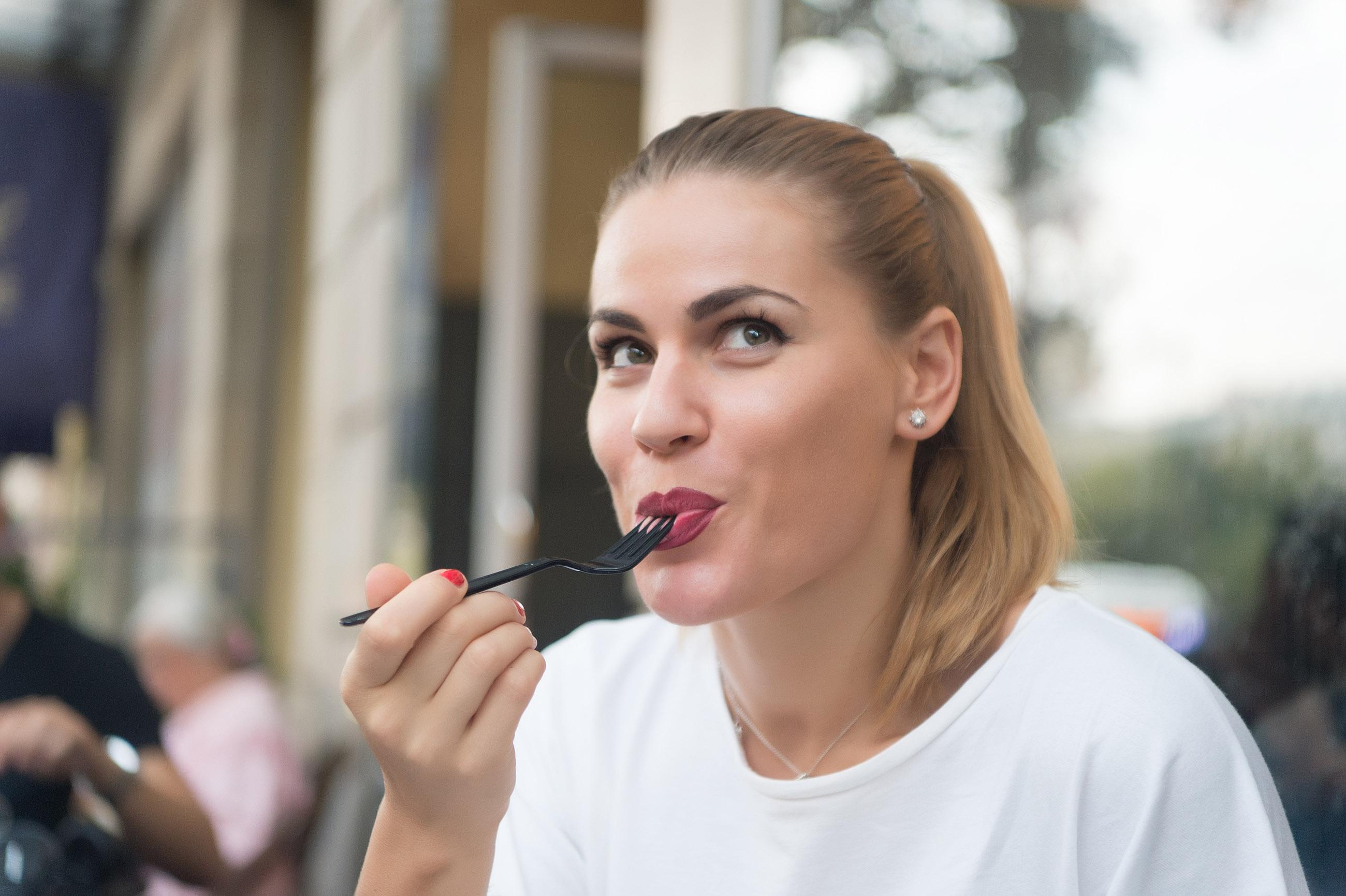 Retrato de una joven mirando hacia arriba con picardía mientras come algo con un tenedor. Por lo que se ve al fondo, parece estar sentada en un restaurante.