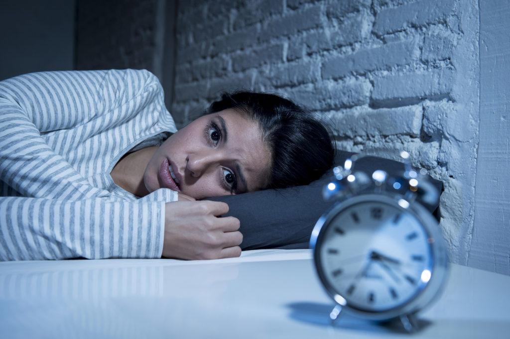 Foto einer Frau, die im Bett liegt und ängstlich einen Wecker anstarrt, der sich vor ihr befindet.