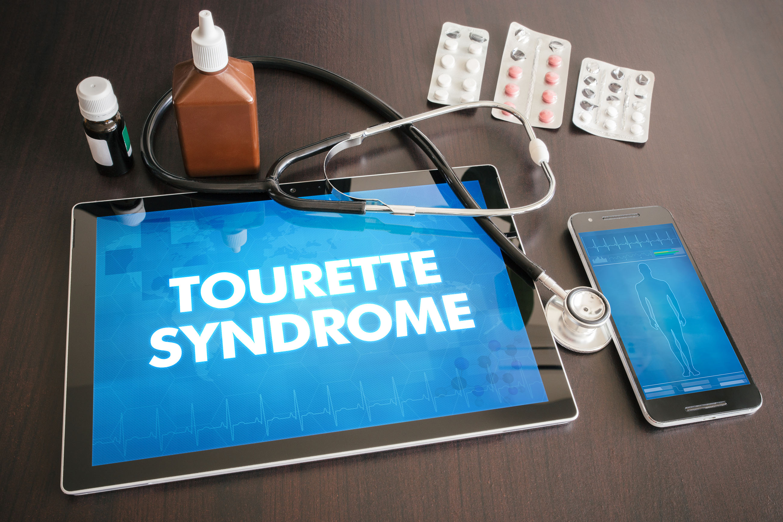 "Photo of a table containing a tablet, a mobile phone, a stethoscope, some pills and two bottles. On the tablet are the words ""Tourette Syndrome"", while the mobile phone shows the outline of a person."