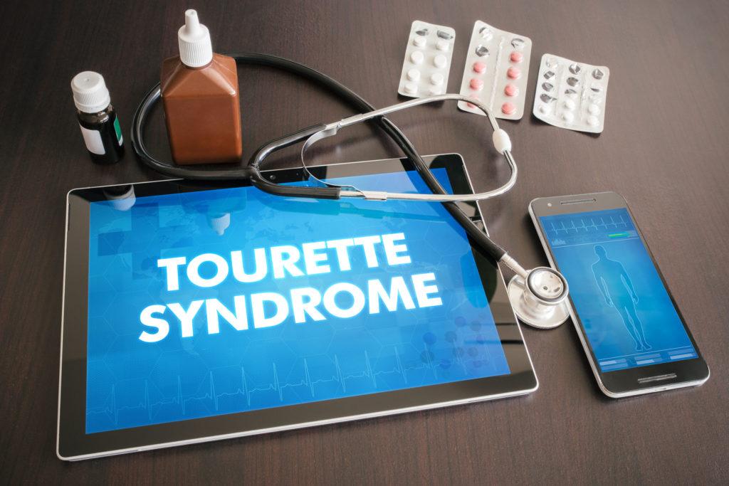 """Foto einer Tischoberfläche, auf dem sich ein Tablet, ein Mobiltelefon, ein Stethoskop, Tabletten und zwei Flaschen befinden. Auf dem Tablet ist """"Tourette Syndrome"""" zu lesen, auf dem Mobiltelefon ist der Umriss eines Menschen abgebildet."""