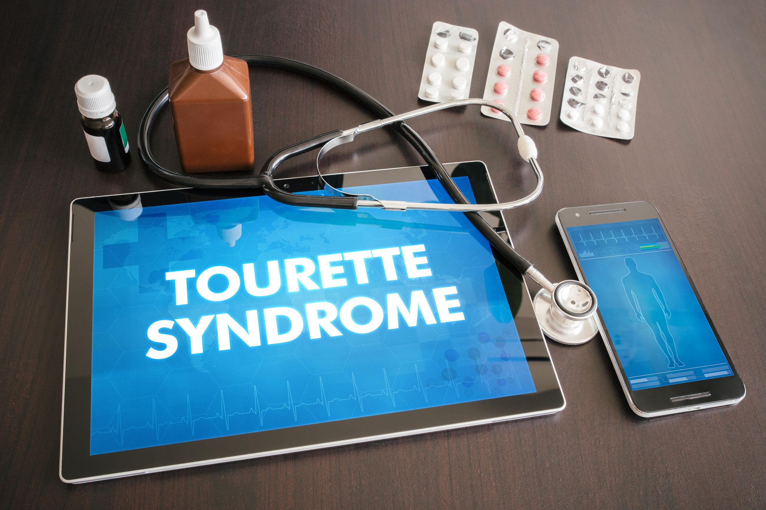 Fotografía de una mesa sobre la que se encuentran una tableta, un teléfono móvil, un estetoscopio, varias pastillas y dos frascos. En la tableta vemos las palabras «Tourette Syndrome» (síndrome de Tourette), mientras que el móvil muestra la silueta de una persona.