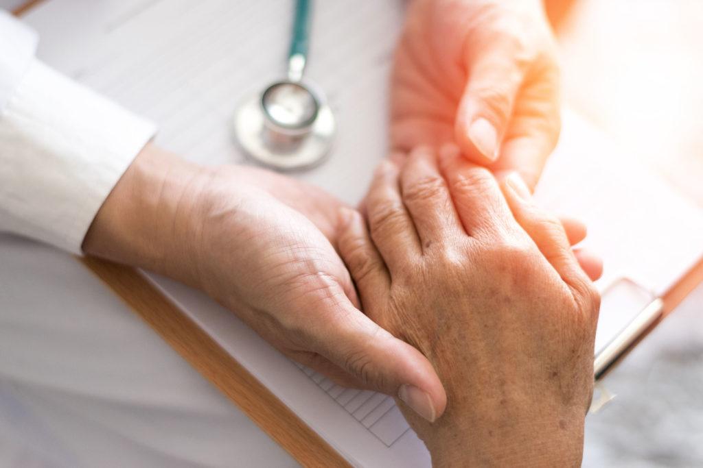 Auf dem Foto ist die Hand eines älteren Menschen zu sehen, die von zwei anderen Händen berührt werden. Weiße Ärmel und ein Stethoskop deuten darauf hin, dass es sich um die Untersuchung bei einem Arzt handelt.