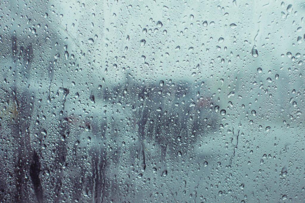 Close-up van een regenachtig venster met regendruppels die langs het raam naar beneden rollen.