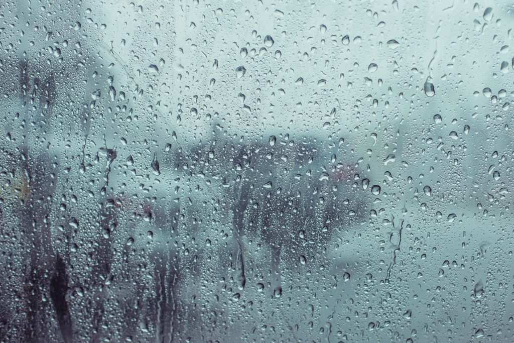 Nahaufnahme einer verregneten Fensterscheibe, auf der Wassertropfen sichtbar sind.